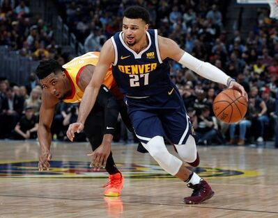 Denver Nuggets guard Jamal Murray, front, drives past Utah Jazz guard Donovan Mitchell during the first half of an NBA basketball game Thursday, Feb. 28, 2019, in Denver. (AP Photo/David Zalubowski)
