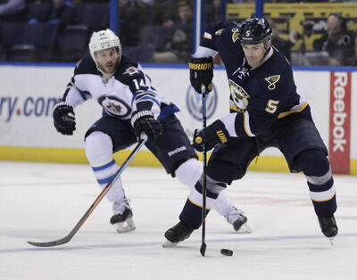 St. Louis Blues' Barret Jackman (5) controls the puck as Winnipeg Jets' Anthony Peluso (14) defends during the first period Tuesday in St. Louis.