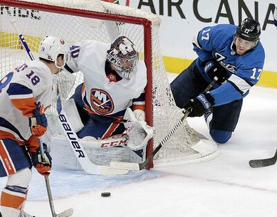 Winnipeg Jets' Adam Lowry tries a wrap around against New York Islanders Goalie Semyon Varlamov at Bell MTS Place, Thursday.