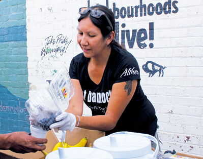 Althea Guiboche pours a cupful of blueberries to one of more than 100 people who line up each week at Dufferin and Main to receive a healthy meal Guiboche prepares with the help of friends and volunteers.