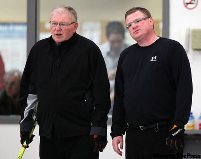 Jim Kirkness (left) and son James watch proceedings at the Mani­toba Mixed Curling Cham­pionship at the Stonewall Curling Club.