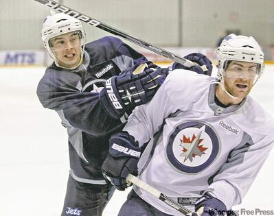 Mike Deal / Winnipeg Free PressJets forwards Tim Stapleton (left) and Jim Slater tangled during Wednesday�s practice at the MTS Iceplex.