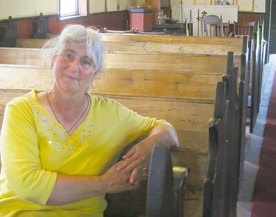 Church warden Monica Griffiths inside the historic log St. Anne's Anglican Church in Poplar Point. The congregation celebrates its 153th anniversary Sunday.