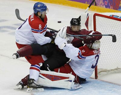 Czech Republic's Michal Barinka (8) and Latvia forward Martins Karsums visit Ondrej Pavelec in the Czech goal in the second period Friday.