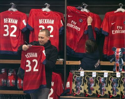 ADDS THE NAME OF THE CLUB A man looks at a soccer shirt on display with the name of British soccer player David Beckham, at the the Paris Saint-Germain club's shop on the Champs Elysees, in Paris, Friday, Feb. 1, 2013. The jersey is on sale for euros 110 ($150). David Beckham lit up a subdued transfer deadline day in Europe by securing perhaps the final move of his globetrotting career, a surprise short-term deal with ambitious French club Paris Saint-Germain. (AP Photo/Michel Euler)