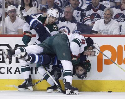 Winnipeg Jets&#39; Mathieu Perreault (85) gets checked by Minnesota Wild&#39;s Nick Seeler (36) and Jason Zucker (16) during second period NHL game one playoff action in Winnipeg on Wednesday, April 11, 2018. (John Woods / The Canadian Press)</p>