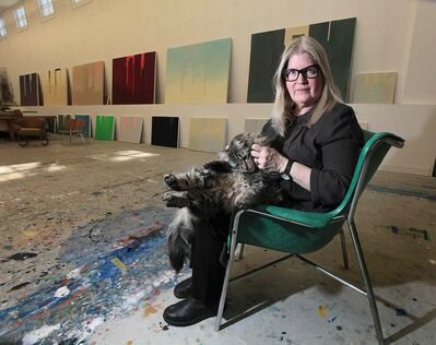 Flanked by some of her large canvasses, Winnipeg artist Wanda Koop nuzzles her cat George. (Phil Hossack / Winnipeg Free Press files)
