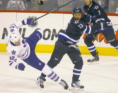 Melissa Tait / Winnipeg Free PressJets forward Dustin Byfuglien sends Leafs forward Troy Bodie flying in the second period at the MTS Centre Saturday night.
