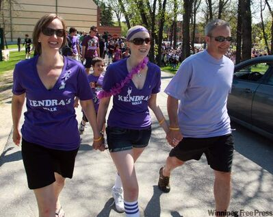 Kendra McBain (centre) takes part in the first Kendra's Walk last year with mother Tammy and dad Rob.