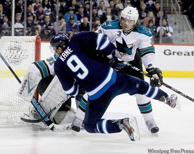 TREVOR HAGAN / WINNIPEG FREE PRESSWinnipeg Jets winger Evander Kane is given a rough ride by San Jose�s Douglas Murray in front of the Sharks� goal during second-period action.
