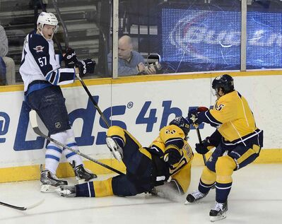 Winnipeg Jets defenceman Tyler Myers (57) collides with Nashville defenceman Anton Volchenkov (20) as centre Craig Smith, right, looks for the puck in the first period of Thursday's game in Nashville, Tenn. It's too early to tell what will be the real impact of the trade that brought Myers to Winnipeg, Gary Lawless writes.
