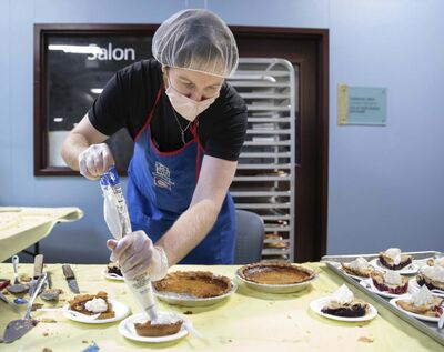JESSICA LEE / WINNIPEG FREE PRESS</p><p>Dallas Holden, a staff member, adds whipped cream to plates of pie at Siloam Mission on Friday when the organization fed dozens of community members Thanksgiving lunch.</p>