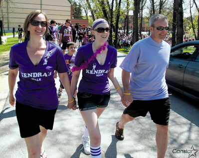 Kendra McBain (pictured centre) walks between her mother, Tammy, and father, Rob, during the first Kendra's Walk in 2009.