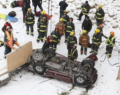 Emergency crews surround car after fatal fall.
