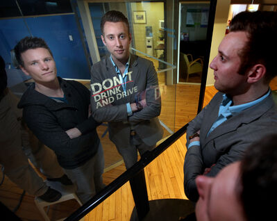 Kris Luinenburg, left, and Bryce North of Advolve stand in front of Mirage Mirror. Sensor-activated images appear in the mirror — in this case, an anti-drinking and driving campaign.