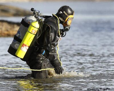 An RCMP Underwater Recovery Team diver searches  the Red River for the vehicle on Thursday.
