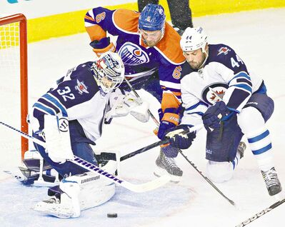 Jets goalie Eddie Pasquale makes the save as Zach Bogosian and Edmonton Oilers' Jesse Joensuu battle for the rebound in their pre-season contest Monday.