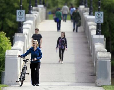 PHIL HOSSACK / WINNIPEG FREE PRESS</p><p>Sylvie Roy, walking her bike across the Assiniboine Park pedestrian bridge, says helmets are a good idea but she hasn't found one she likes.</p>