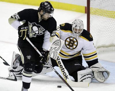 Boston Bruins goalie Tim Thomas, right, blocks a first-period shot by Pittsburgh Penguins' Eric Tangradi (25) during an NHL hockey game in Pittsburgh, Sunday, March 11, 2012.