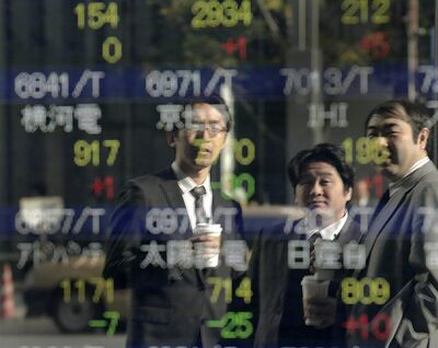 Men look at the electronic stock board of a securities firm in Tokyo, Tuesday, Dec. 18, 2012. Asian stock markets were mostly higher Tuesday, boosted by signs China's recovery is gaining traction and hopes for a new stimulus in Japan. (AP Photo/Itsuo Inouye)