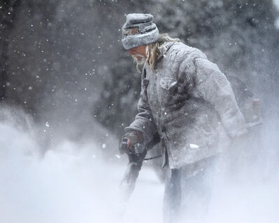 Larry clears a friend's sidewalk of snow with a leaf blower on Jefferson Avenue Saturday afternoon. Snowplows have been out clearing the roads, but it's slippery, so be careful out there.