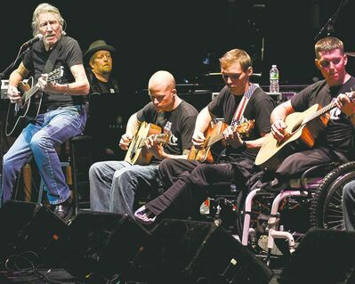 Roger Waters (left) performs with U.S. vets at a fundraising concert.
