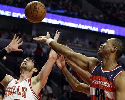 FILE - In this April 17, 2013 file photo, Washington Wizards center Jason Collins, right, battles for a rebound against Chicago Bulls guard Kirk Hinrich during the first half of an NBA basketball game in Chicago. Jason Collins has become the first male professional athlete in the major four American sports leagues to come out as gay. Collins wrote a first-person account posted Monday on Sports Illustrated's website. The 34-year-old Collins has played for six NBA teams in 12 seasons. He finished this past season with the Washington Wizards and is now a free agent. He says he wants to continue playing. (AP Photo/Nam Y. Huh, File)