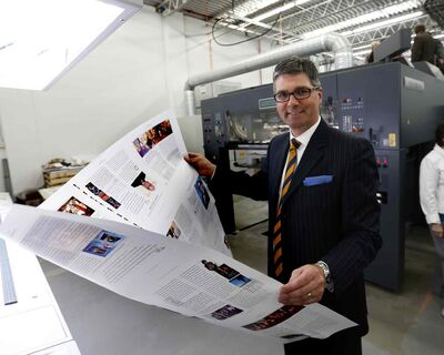 Friesens Corp. CEO Curwin Friesen examines a full-colour product sheet run off the company's new press Tuesday in Altona.