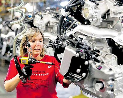 An auto worker assembles a Camaro engine at the GM factory in Oshawa, Ont.
