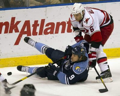 Florida Panthers' Stephen Weiss (9) and Carolina Hurricanes' Tim Gleason (6) battle for the puck during the first period of an NHL hockey game in Sunrise, Fla., Sunday, March 11, 2012.