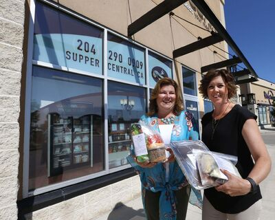 WAYNE GLOWACKI / WINNIPEG FREE PRESS</p><p>Lori Vassart (right) holds Bruschetta Pasta and Hollow Mushroom Stuffed Burgers meals while Crystal Anderson shows off Nacho Packs in front of their Supper Central store in Kenaston Common.</p>