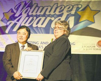 Lt.-Gov. Philip Lee presents a Lieutenant-Governor's Make a Difference Community Award to Randi Gage.