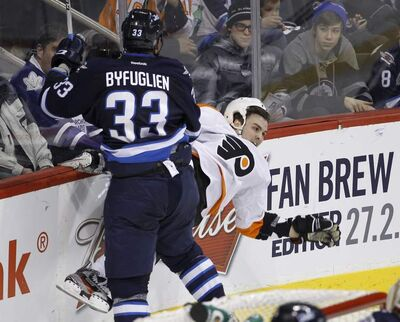 Winnipeg Jets' Dustin Byfuglien (33) crushes Philadelphia Flyers' Zac Rinaldo (36) into the boards during second-period NHL hockey action in Winnipeg on Tuesday.