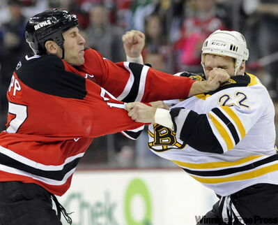 New Jersey Devils' Mike Rupp, left, fights with Boston Bruins' Shawn Thornton.