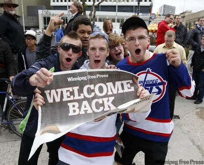 Tyller Ilagan, Jamie Turek and Taylor Allen cheer the return of the NHL at Canwest Place, near Portage and Main.