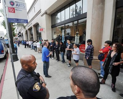 Apple saleman talks to the crowd waiting to purchase new iPhones at Apple Store in Pasadena Friday, Sept. 20, 2013. Police detained three people after a fight erupted outside Apple Store,where a crowd waited overnight for release of the new iPhone. The fight was over homeless people who were promised $40 and didn't get paid, to wait overnight to purchase iPhones for a buyer.(AP Photos/ San Gabriel Valley Tribune, Walt Mancini)
