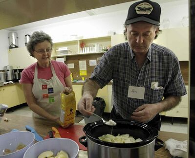 Instructor Judy Dikkema gives Ron Redding some cooking tips for his pork and apple casserole.