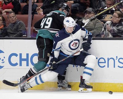 Winnipeg Jets defenceman Tyler Myers, right, and Anaheim Ducks left wing Max Jones fight for the puck during the second period.