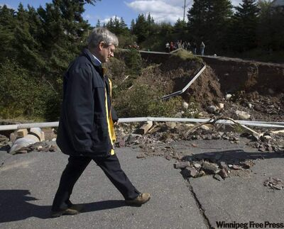 Prime Minister Stephen Harper checks out hurricane damage on a washed-out road during a visit to Britannia, N.L., on Friday.
