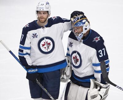 Winnipeg Jets goaltender Connor Hellebuyck (37) gets a pat on the head from teammate Adam Lowry (17) after their overtime NHL Stanley Cup playoff hockey loss to the Montreal Canadiens, in Montreal, Monday, June 7, 2021. THE CANADIAN PRESS/Ryan Remiorz