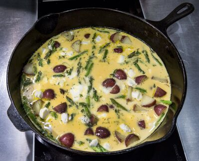 After the base ingredients are sauteed, pour in the eggs for a savory frittata.