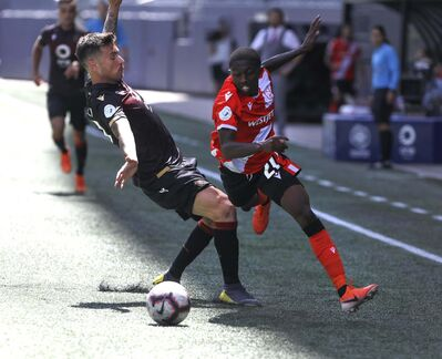 RUTH BONNEVILLE / WINNIPEG FREE PRESS FILES</p><p>Calvary FC's Malyk Hamilton (right) is marked by Valour FC's Michele Paolucci during their CPL game on Saturday.</p></p>
