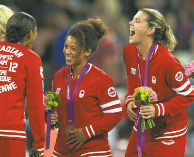 Canadian soccer stars Desiree Scott, of Winnipeg,  and Christine Sinclair (right) celebrate Olympic bronze-medal win.