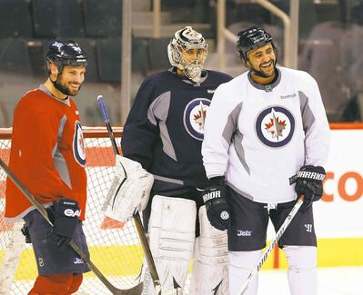 Dustin Byfuglien (right, with Zach Bogosian and Ondrej Pavelec) practised Thursday as a forward, fuelling speculation he might move up.