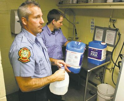 Winnipeg firefighters and paramedics prepare water jugs for delivery at Winnipeg Fire and Paramedic Station 22, 1567 Waverley St. Jay Simons and Dale Worrall demonstrate how they are going to clean and fill the water jugs.