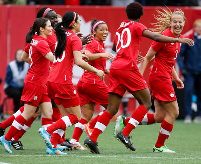 Getting  their kicks  Team Canada midfielder Desiree Scott (centre) celebrates with defender Kadeisha Buchanan (20), who scored, defender Rebecca Quinn (3) and other teammates after Canada went ahead 1-0 in the first half of a soccer friendly against Team USA Thursday night at Investors Group Field. The Americans scored a late goal to salvage a 1-1 tie.