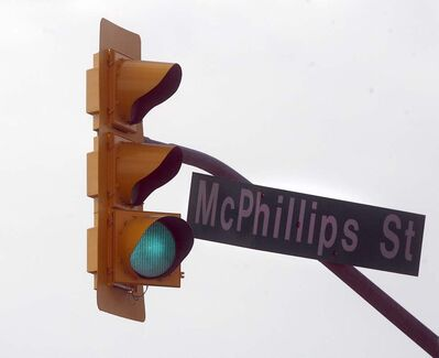 A traffic light signal sways in 70 km/hr winds on McPhillips Street at Mountain Avenue in a 2013 file photo.