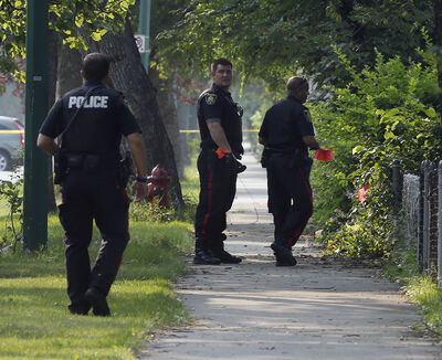 Police investigate the crime scene on Thursday. They're not saying whether a firearm was found inside the house.