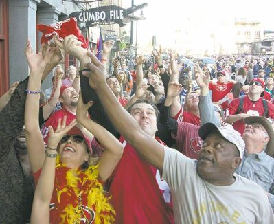 george bridges / mctFans grab at San Francisco 49ers towels thrown from a balcony on a jam-packed New Orleans street Saturday.