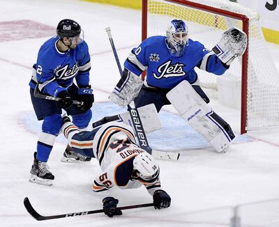 Winnipeg Jets goaltender Laurent Brossoit (30) makes a save as Edmonton Oilers' Kailer Yamamoto (56) is dumped by Dylan DeMelo (2) in front of the net during the first period. (Fred Greenslade / The Canadian Press)